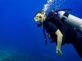 Woman tourist diver in descent to reef scuba diving under water